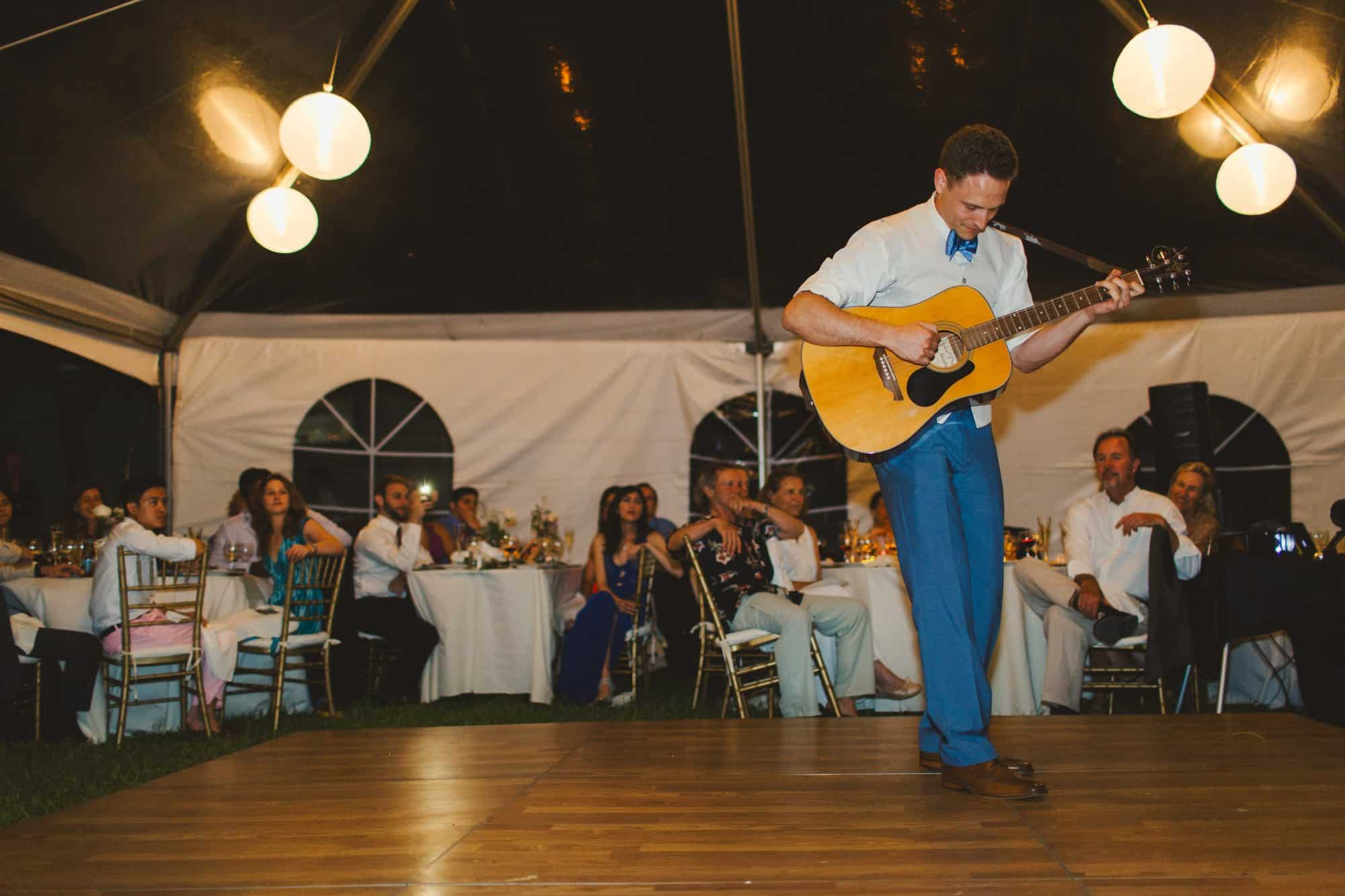 groom playing guitar on wedding day in maui